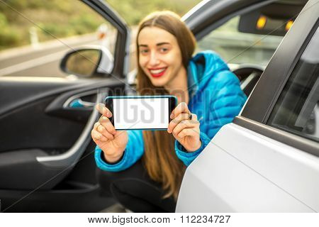 Woman showing phone sitting in the car