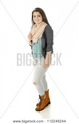 A beautiful teen girl happily standing in her holey jeans, eternal scarf and lace-up, zipper-up boots.  On a white background.