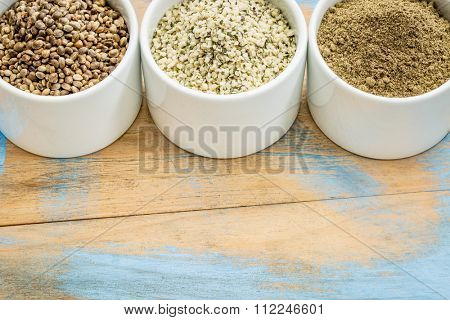 hemp products: seeds, hearts (shelled seeds) and protein powder in small ceramic bowls on a grunge wood with a copy space