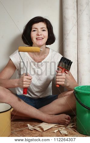 happy woman prepare to make a repair stick wallpapers with rollercoaster and clue