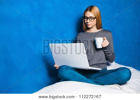 Nice Portrait Of Beautiful Girl On Blue Background. Young Woman With Glasses Sitting Cosily, Holding
