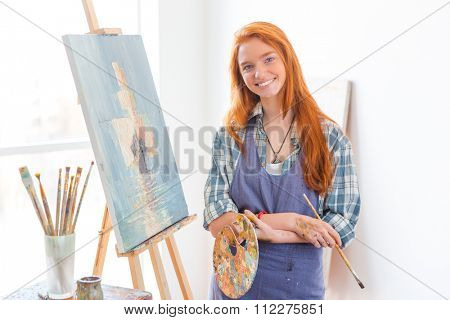 Happy satisfied beautiful young woman painter in apron finished painting picture in art studio
