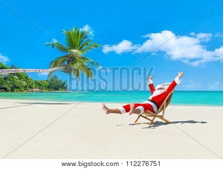 Christmas Santa Claus On Deckchair Enjoing Palm Sady Ocean Beach