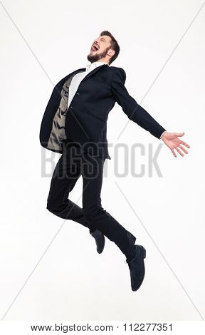 Excited elated happy young business man with beard in classic suit jumping and shouting over white background