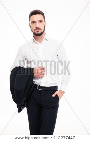 Handsome confident young businessman with beard in black siut and white shirt standing and holding jacket over white background