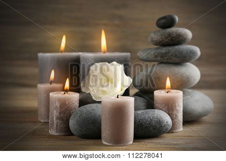 Alight wax grey candle with pebbles and beautiful flower on wooden background