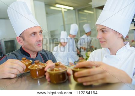 Chef and trainee picking up ramekins