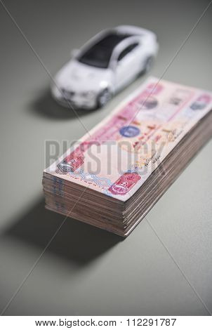 'Car loan' - creative concept. Stack of UAE dirham notes and a toy car in background.