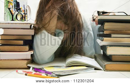people, education, session, exams and school concept - tired student girl or young woman with books sleeping . The night before the exam