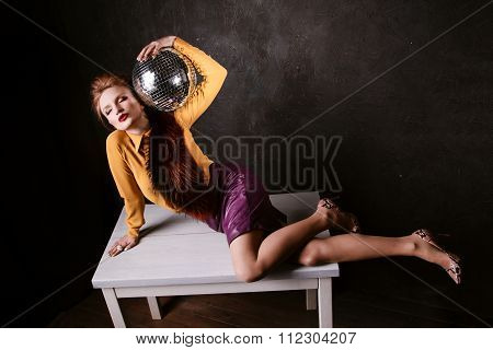 Studio Shoot Of Posing Woman Holding Disco Ball.  Retro Style.