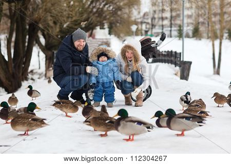 Happy Young Family Walking In A Winter Park