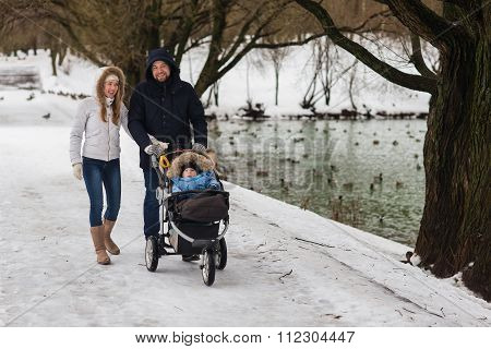 Happy Young Family Walking In The Park In Winter