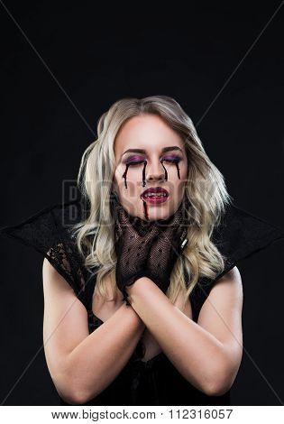 Beautiful blonde girl vampire is strangling herself