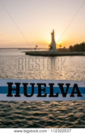 Ribbon with the colors of Huelva and in the background out of focus, the Columbus Monument