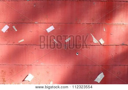 Closeup of red wooden texture of board with staples and scarp of paper. Morning sunshine on board.