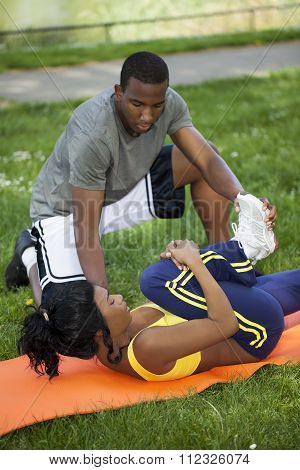 Black Woman Stretching On Orange Pad With Man
