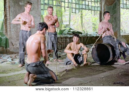 five young men in ragged pants with rope in his hands in abandoned building, focus on the left man