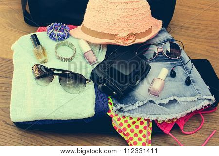 Open the suitcase with tourist things: women's hat, swimsuit, camera, denim shorts, dresses, sunglas