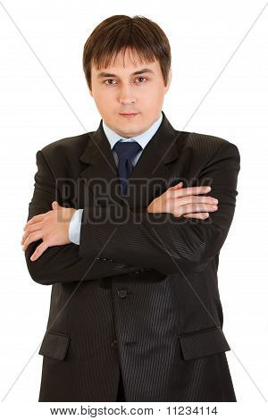 Serious young businessman with crossed arms on chest isolated on white