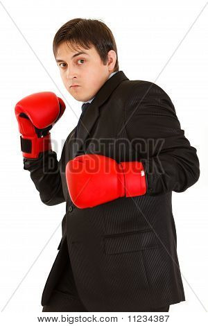 Punching furious young businessman with boxing gloves isolated on white