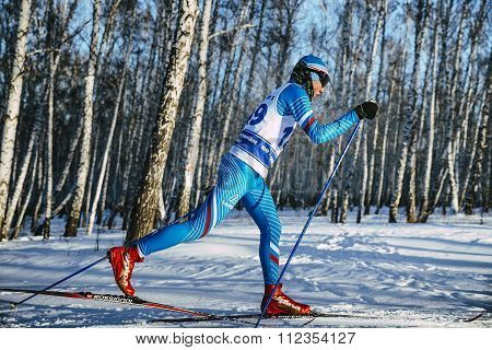 side view young skier athlete winter birch forest sprint race in classic style