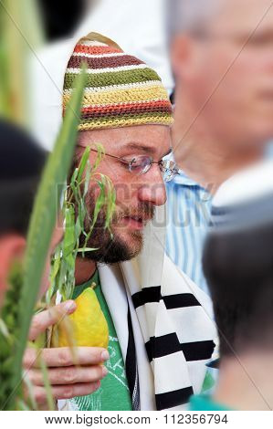 JERUSALEM, ISRAEL - SEPTEMBER 20, 2013:  Young religious Jew in a knitted skullcap and talite with citrus-etrog praying in the morning of Sukkot. The Western Wall of the Temple in Jerusalem