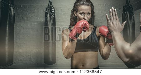 Female boxer with fighting stance against trainer hand against punching bags in red boxing area