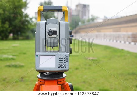 Measuring instrument for topographic and geodetic shooting in front of green grass and buildings