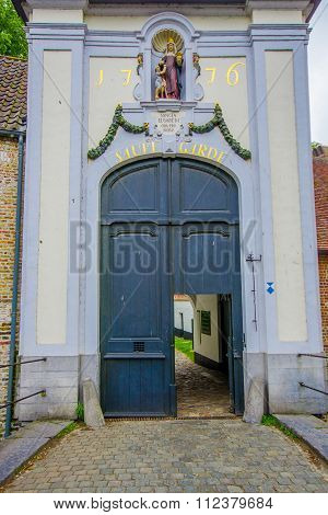 BRUGES, BELGIUM - 11 AUGUST, 2015: Door entrance to famous beguinage with the words Sauve Garde writ