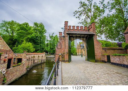 BRUGES, BELGIUM - 11 AUGUST, 2015: Small waterchannel sorrounded by brick walls green vegetation, la
