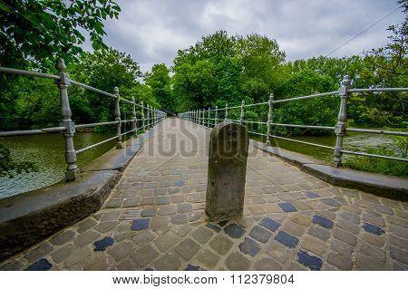 BRUGES, BELGIUM - 11 AUGUST, 2015: Bridge stoned pedestrian bridge passing water channel inside gard