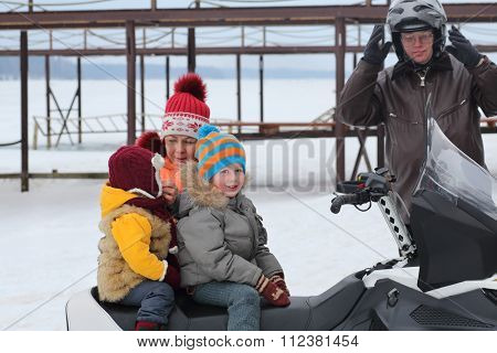 The mother prepares two children to ride with his father on a snowmobile, focus on boy