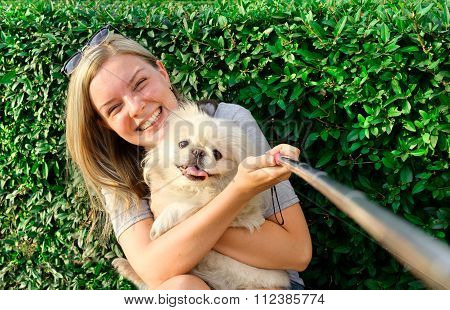 Beautiful girl with dog taken pictures of her self
