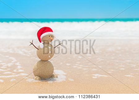 Sandy Christmas Snowman In Santa Hat At Ocean Beach Sand