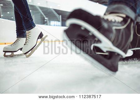 Man's hockey skates and women's figure skates on ice background