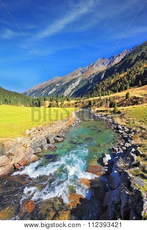 National Park Krimml Waterfalls in Austria. Headwaters of waterfalls - the narrow fast roiling river among green mountain meadows