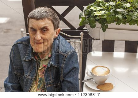 Elderly disabled man with cerebral palsy sitting in a street cafe.
