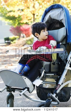 Disabled boy with cerebral palsy in medical stroller