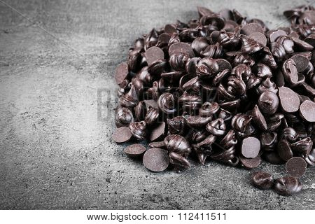 Chocolate morsels on gray background
