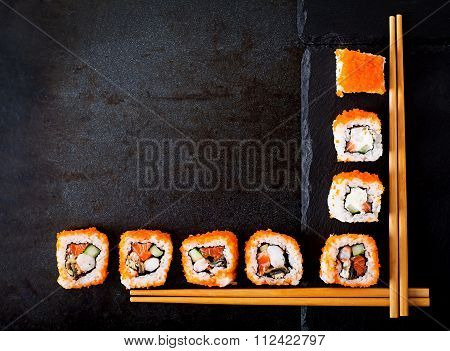 Traditional Japanese Food - Sushi, Rolls And Chopsticks For Sushi On A Dark Background. Top View