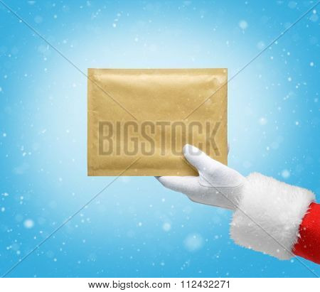Hand in costume Santa Claus is holding the envelope / studio shot of man's hand holding yellow envelope / Merry Christmas & New Year's Eve concept / Closeup on blurred blue background.