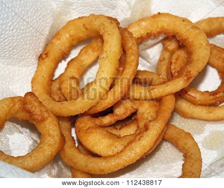 Golden brown deep fried Onion Rings set on paper towel to absorb grease