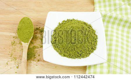 Japanese matcha green tea powder on the spoon on wooden board