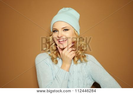 Gorgeous young woman with blond ringlets in a green knitted winter outfit smiling,over light brown