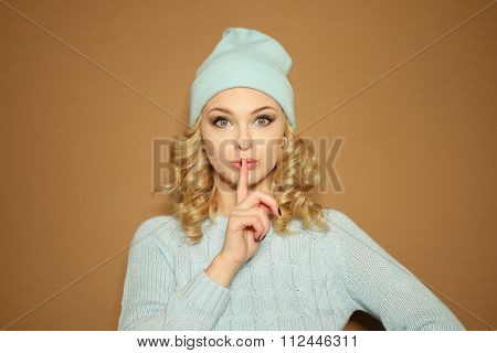 Gorgeous young woman with blond ringlets in a green knitted winter outfit making a shushing gesture with her finger to her lips as she asks for silence, over light brown