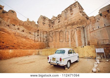 White Retro Car Parked In Yard Of Historical Jaisalmer Fort Built In 1156 Ad