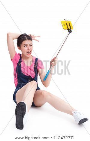 Young woman taking picture with smartphone selfie stick and sitting on the floor.