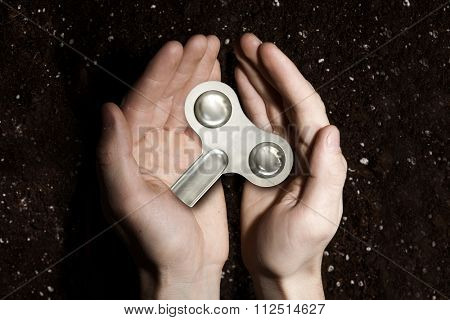 Male hands holding key winder on soil background
