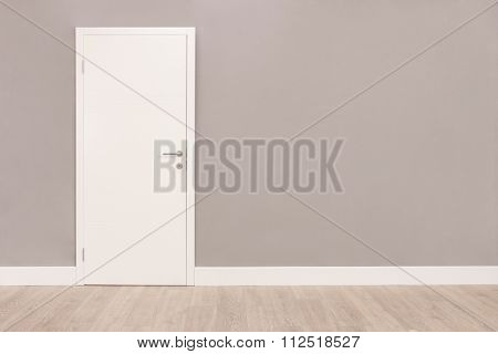 Shot of a closed white door on a gray wall in an empty room