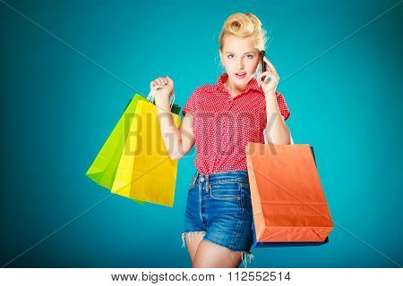 Pinup blond girl young woman in retro style calling on the mobile phone. Client customer holding colorful paper shopping bags on vibrant blue. Retail and sale. Studio shot. poster